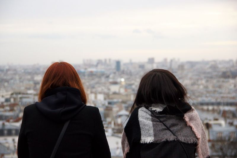 Rear view of women looking at cityscape against sky