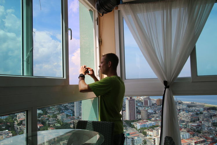 Man Holding Mobile Phone While Standing By Window At Home