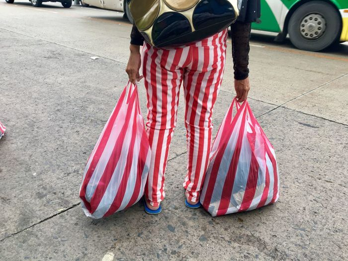 A woman wears a stripes pants matching two plastic stripes shopping bags she is carrying as she waits for a ride along EDSA extension in Pasay City, Metro Manila, Philippines. Low Section Car Day One Person Transportation Outdoors Real People Adult Adults Only Woman Stripes Stripes Pattern Stripes Photography Stripes Straight Lines Stripes Everywhere Red And White Manila, Philippines Manila Pasay City Philippines Streetphotography Street Best EyeEm Shot Bestoftheday