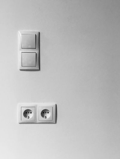 Close-Up Of Electric Outlets And Switches On Wall At Home