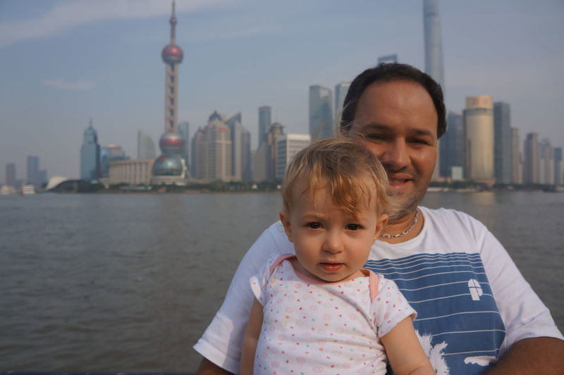 Portrait Of Man And Baby Girl With Oriental Pearl Tower In Background Against Sky