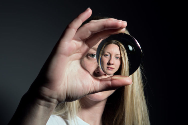 Close-up portrait of woman holding crystal ball with reflection against black background