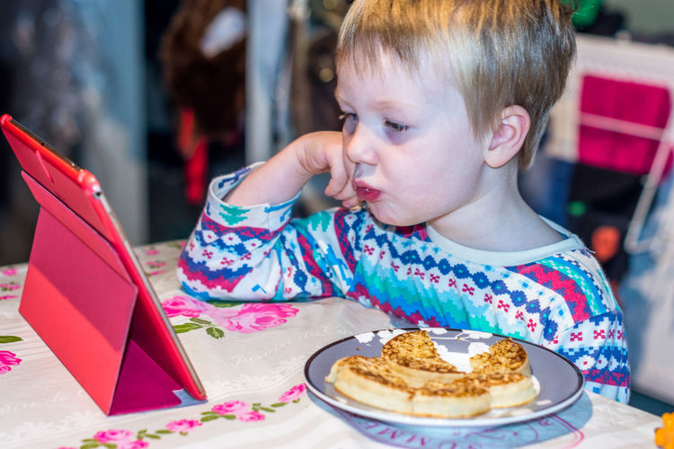 Little Boy watching digital tablet with face expression Blond Hair Childhood Close-up Crumpets Curious Expression Fashion Food Food And Drink Freshness Indoors  Interested Lifestyles One Person Pancakes Plate Ready-to-eat Real People Sitting Sweet Food Table Tablet Watching