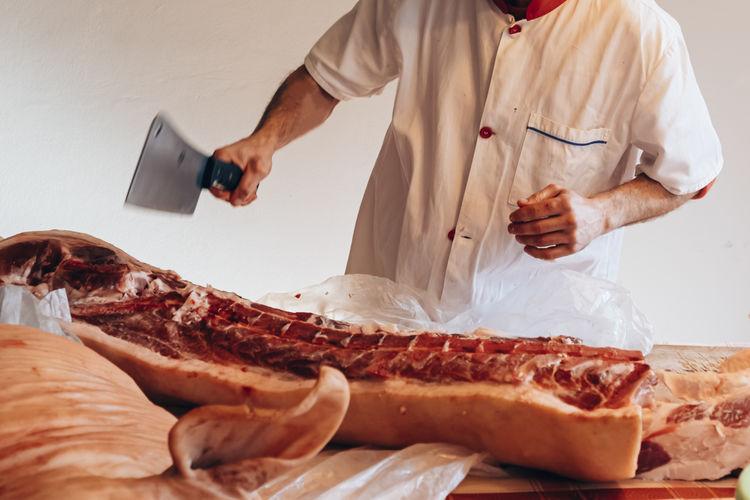 Close up of a butcher cutting a pig carcass