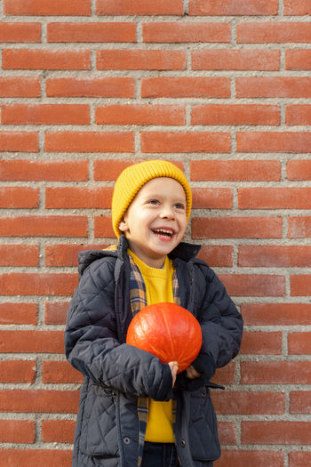 Portrait of a smiling girl standing against brick wall