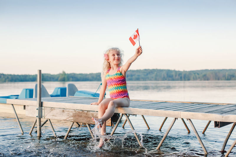 Full length of girl holding canadian flag sitting on pier by lake