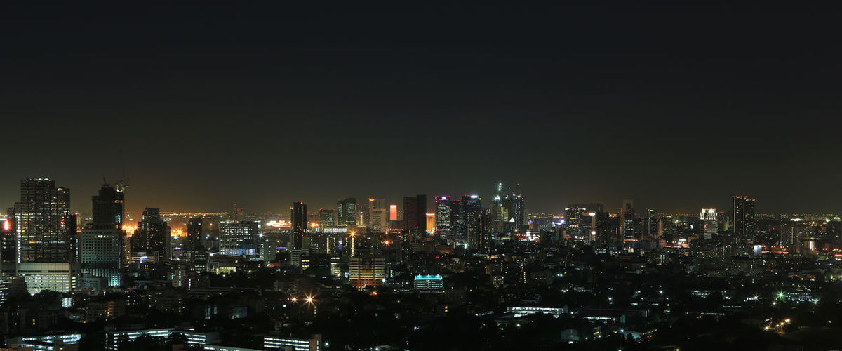 Illuminated buildings in city against sky at night