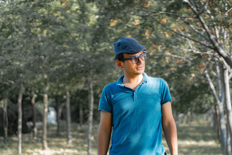 Mature Man Wearing Cap And Eyeglasses Standing Against Trees In Forest