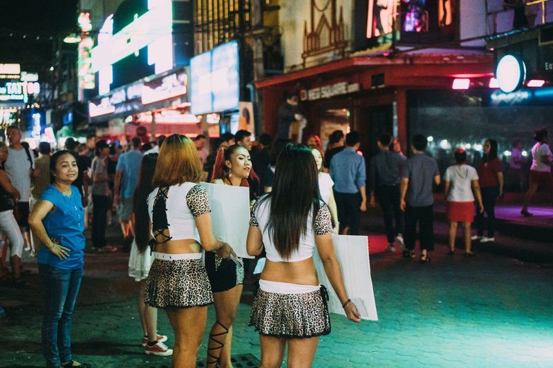 People standing on street in city at night