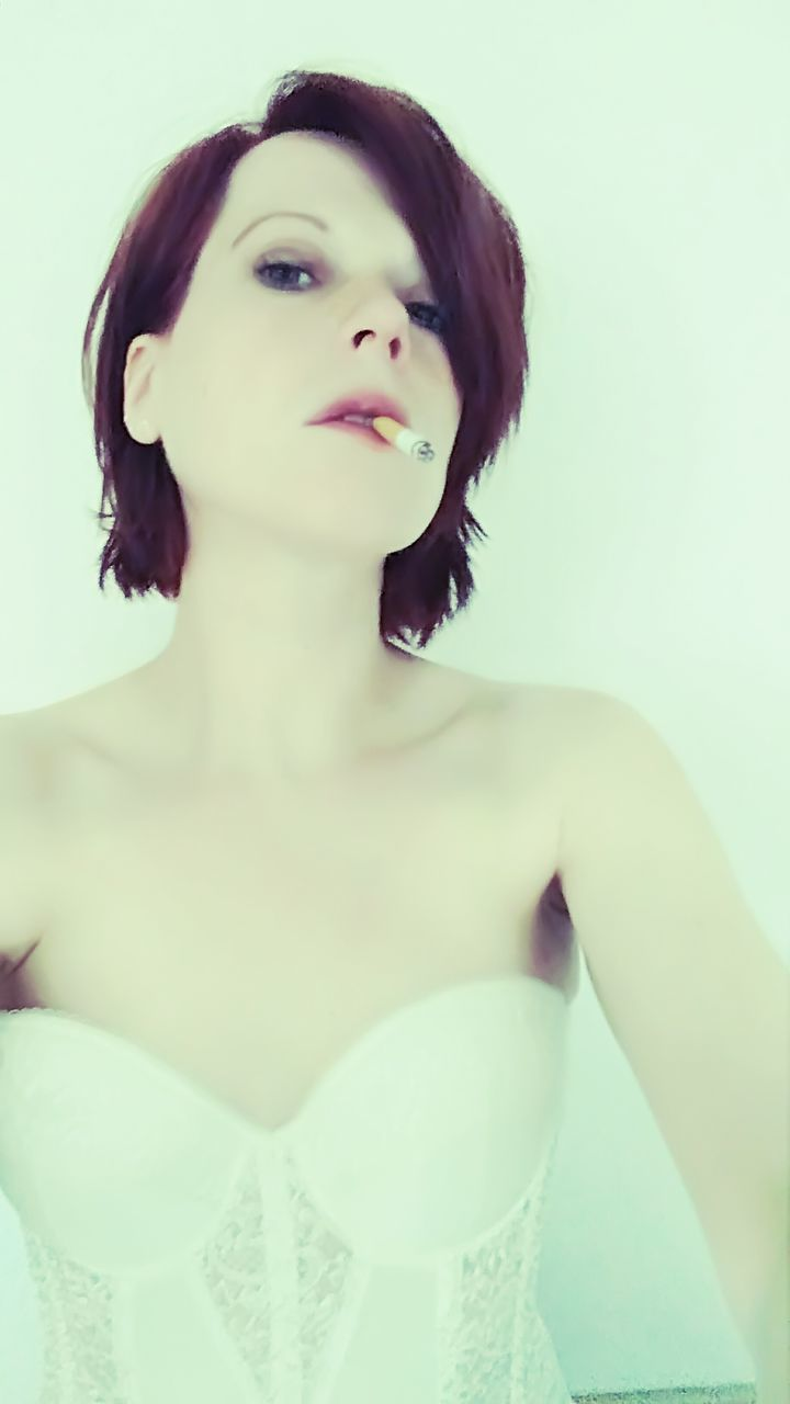 Portrait Of Beautiful Woman Smoking Cigarette Against White Background