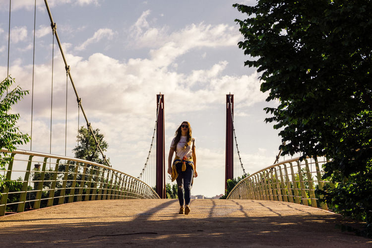Full length of woman on footbridge against sky