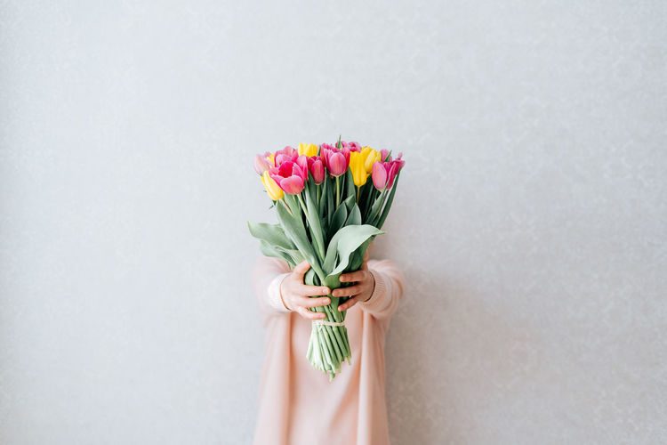 Close-up of hand holding bouquet against white background