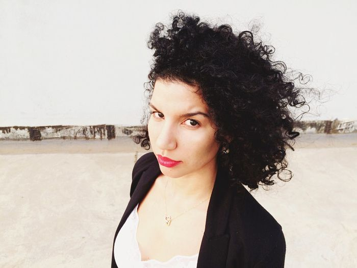 Portrait of young woman with curly hair at beach