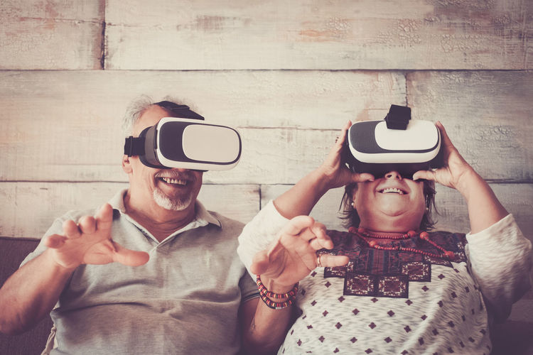 Smiling couple wearing virtual reality simulator while sitting at home