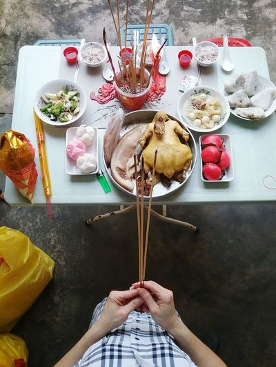 Top view of hands holding joss sticks and food offerings on table during religious prayer Colour Of Life People Pray Praying Oriental Belief Faith Taoism Buddhism Food Top View Hands Holding Joss Sticks Rite Ritual Ghost Festival Hungry Ghost Festival Religious Ceremony A Bird's Eye View The Photojournalist - 2017 EyeEm Awards