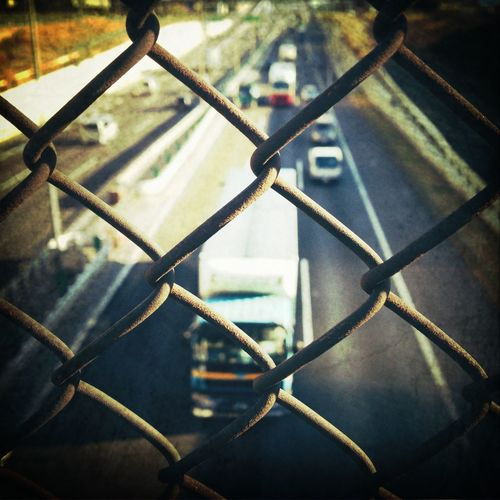 High Angle View Of Truck Moving On Road Seen Through Chainlink Fence