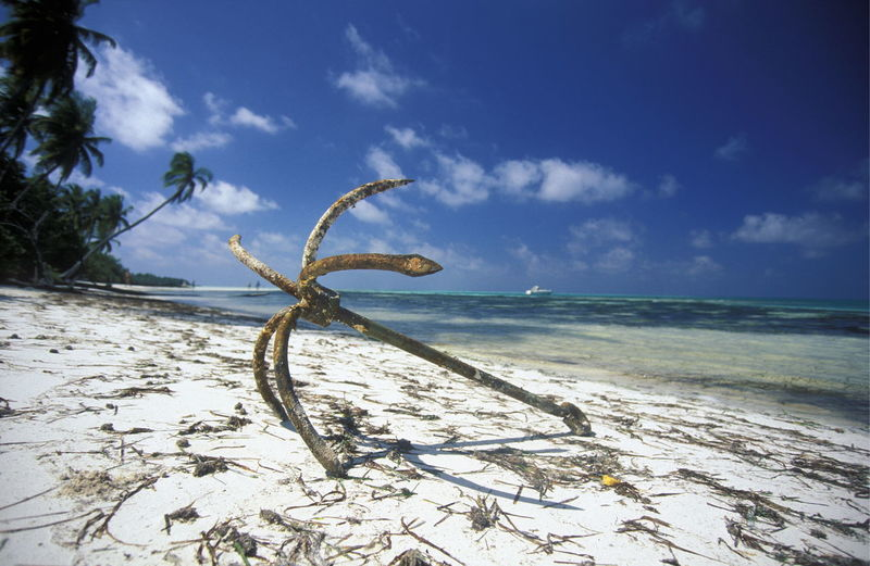 Old abandoned anchor at beach against blue sky on sunny day
