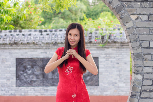 Asian  Woman wearing Traditional Cheongsam Posing Congratulation Gesture during Chinese New Year Festival Outdoor Greetings Gong Xi Fa Cai Culture Red Happy Holiday Dress Qipao Lifestyles Joyful Cheerful Season  Costume