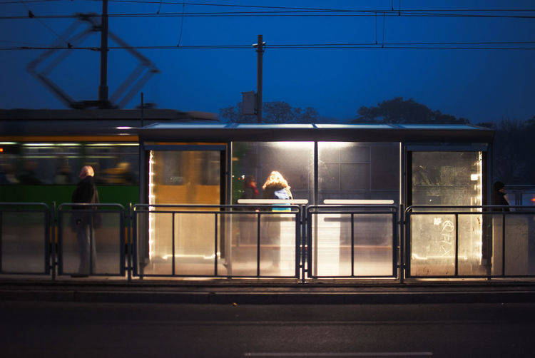 People Traveling In Illuminated Tram At Dusk