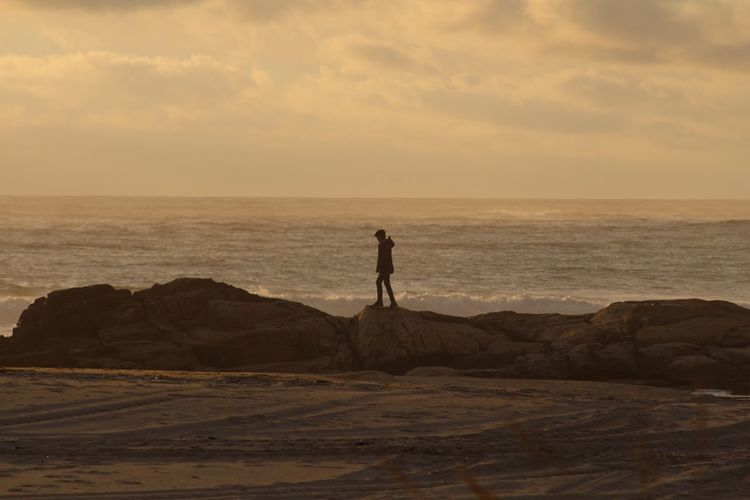 Boy Standing On Rock At Beach During Sunset