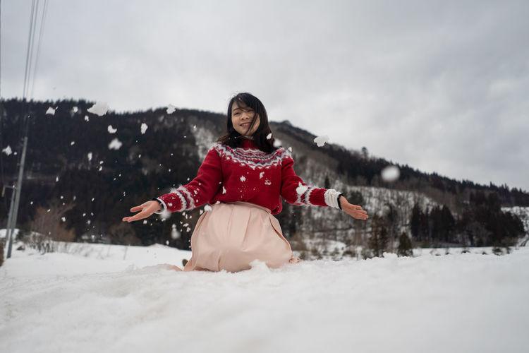 Portrait of smiling woman kneeling on snow