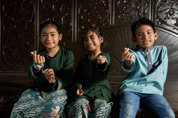 Malay siblings sitting side by side with hand gesture during ramadan festival