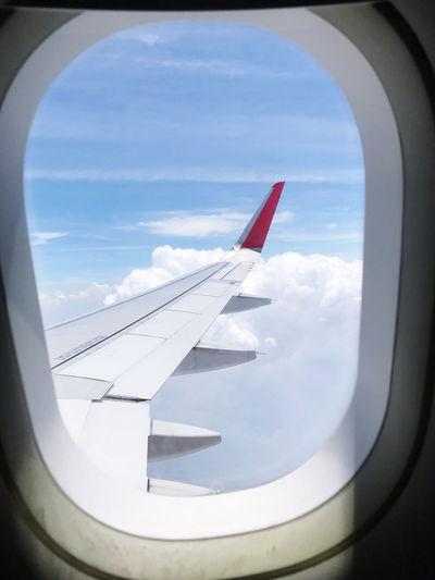 Airplane wing seen through glass window