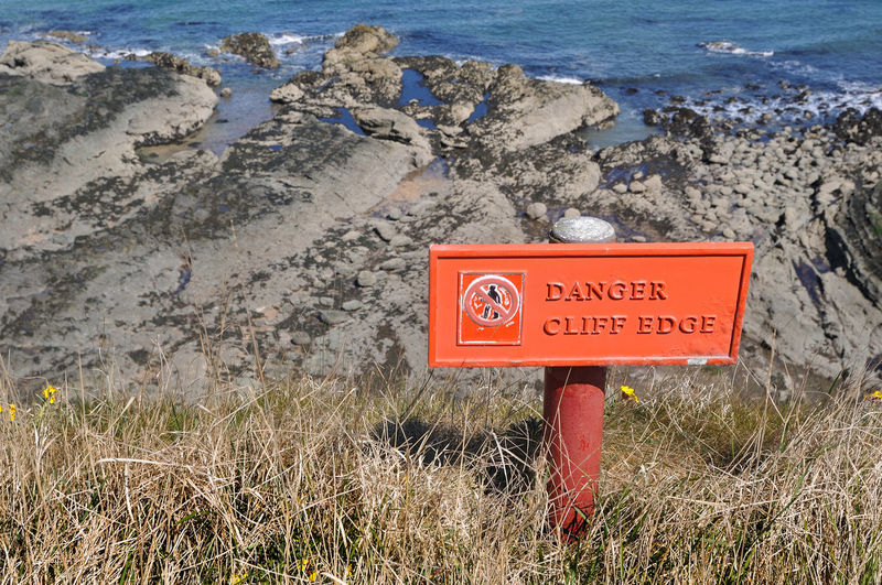 Close-up of warning sign on shore