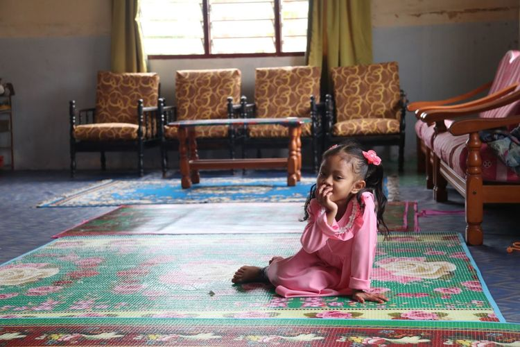 Portrait Of Cute Girl Sitting On Carpet At Home