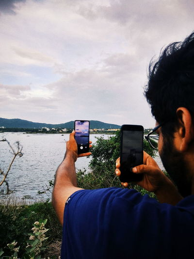 Man photographing lake with mobile phones against sky