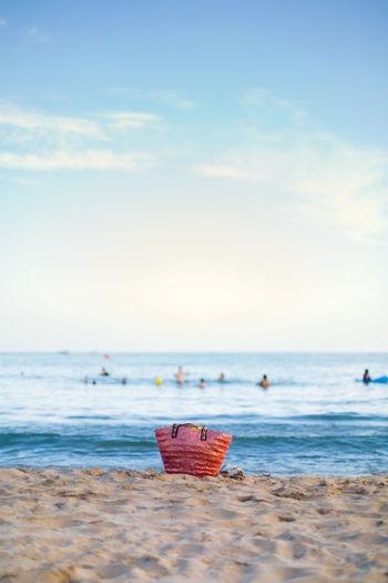 Basket on sand at beach against sky