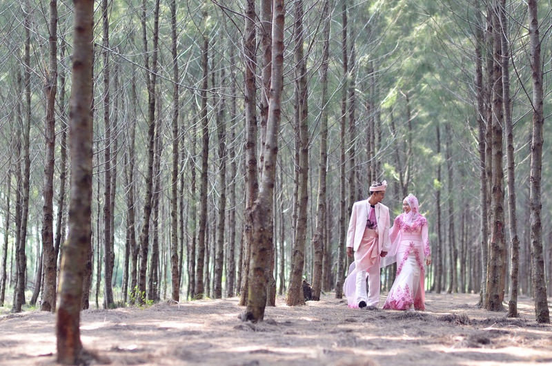 Bride and groom walking amidst trees in forest
