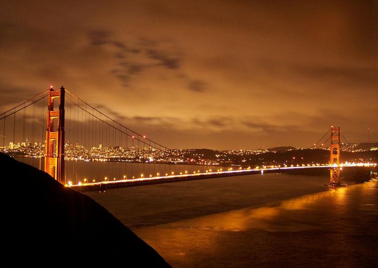Illuminated san franciscooakland bay bridge over sea against cloudy sky at night