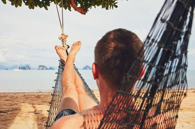 Man Relaxing In Hammock At Beach Against Sky