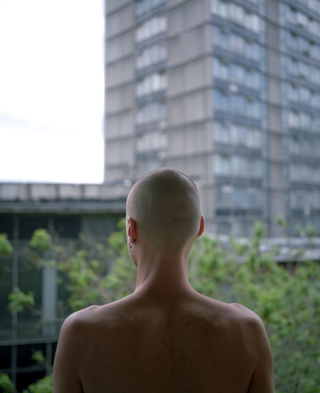 Rear view of shirtless man standing against building in city