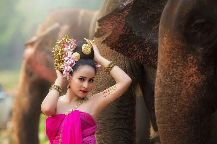 Female In Traditional Clothing Sitting By Elephants