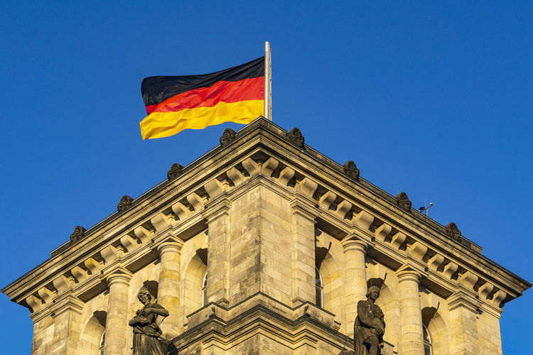 German Flag on Reichstag Building Berlin Germany 🇩🇪 Deutschland Horizontal Color Image Outdoors No People Architecture Built Structure Building Exterior Sky Low Angle View Flag German Flag Clear Sky City Blue The Past History Government Flying Sunlight Famous Place Copy Space