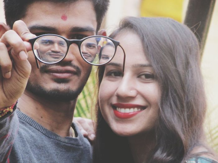 Reflection of smiling young couple in eyeglasses