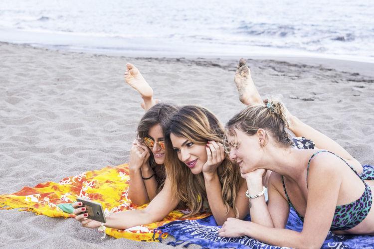 Smiling friends taking selfie at beach