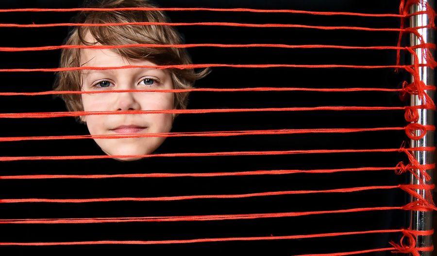 Portrait of boy seen through red threads