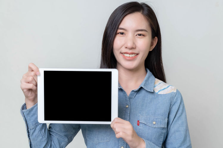 Portrait of smiling young woman using smart phone against white background