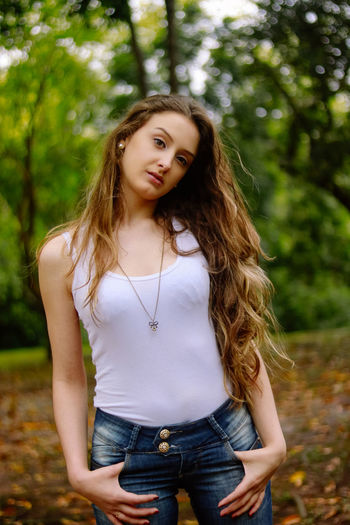 Beautiful Woman Casual Clothing Day Fashion Focus On Foreground Front View Leisure Activity Lifestyles Long Hair Looking At Camera Nature One Person Outdoors Portrait Posing Real People Standing Three Quarter Length Tree Young Adult Young Women
