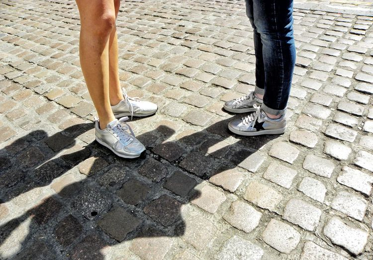 Low Section Human Leg Human Body Part Two People Day Shoe Outdoors Real People Sunlight Standing Lifestyles Textures And Surfaces Summer Sunny Day Chatting Talking Conversation Meeting Friends Summer Clothes Wearing Jeans Day Out Talking With A Friend On The Road Street Stone Road