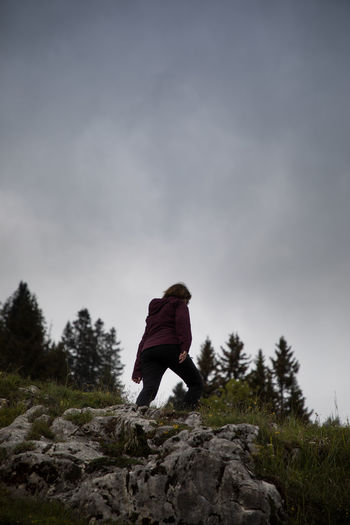 Rear view of person on rock against sky