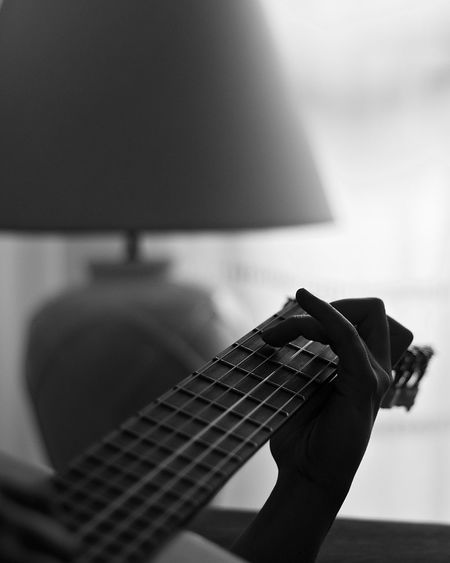 Cropped hand of person playing guitar at home