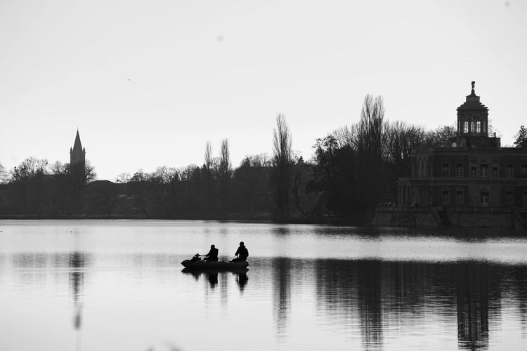 Two people in a. oat on a lake against clear sky
