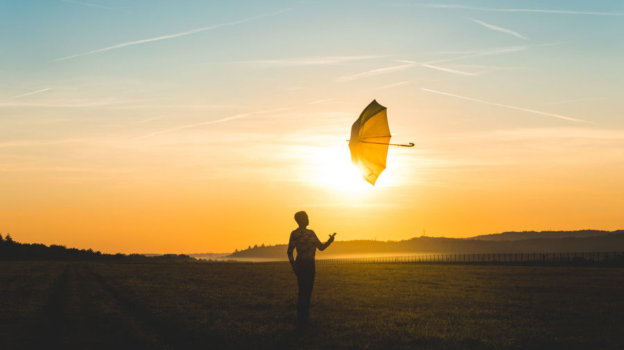 Woman throwing umbrella against sky during sunset
