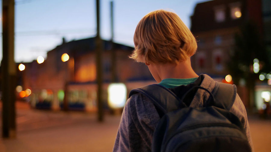 Rear view of boy standing with backpack in city at dusk