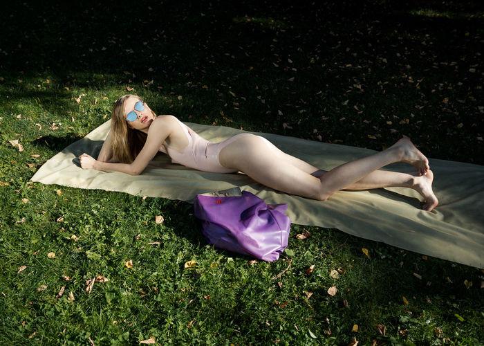 Woman in bikini lying on field