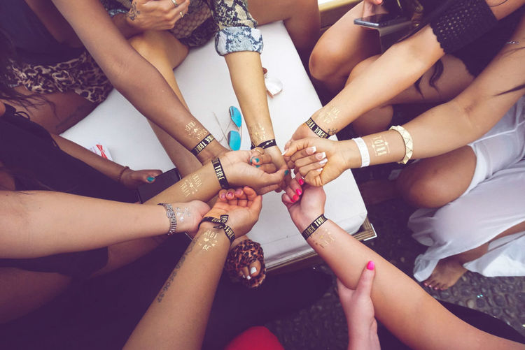 High angle view of female friends showing text on hands during bachelorette party